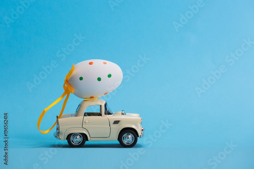 Photo  Toy car carrying easter egg isolated on blue background