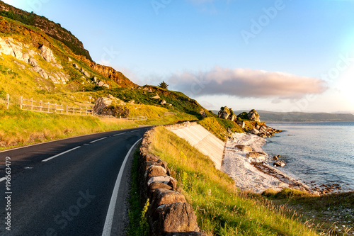 Ingelijste posters Kust The eastern coast of Northern Ireland and Antrim Coastal road a.k.a. Causeway Coastal Route wit rocks and concrete revetment in sunrise light