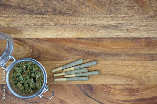 Photo  Weed in jar with cone joints on wood surface