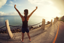 Girl With Arms Outstretched At A Seaside. Beautiful Inspiring Landscape And Sea With Girl And Hands Raised On Sunrise..