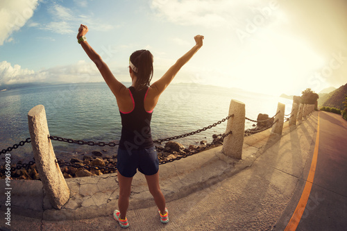 Fotografía  Girl with arms outstretched at a seaside