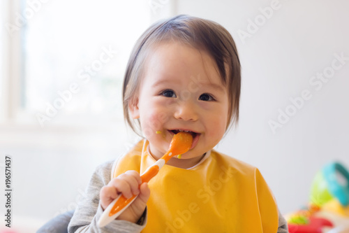 Fototapeta Happy little baby boy eating food in his house obraz