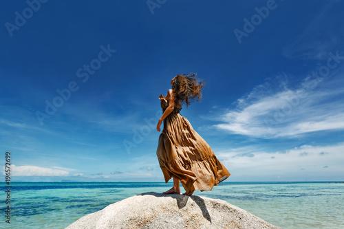Fotografía  beautiful young woman in elegant dress on the beach