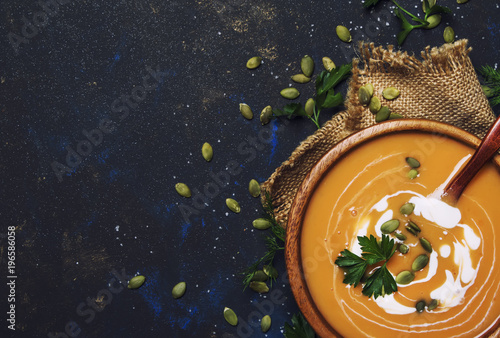 Creamy pumpkin soup in wooden bowl, rustic style, top view
