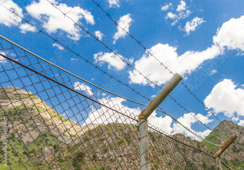 f5b530335bb7 Fence with barbed wire in the open air - Buy this stock photo and ...