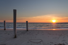 Beautiful Sunset At The Beach With Wooden Piles And Hearts Drawings In The Sand Petten, Holland, North Sea