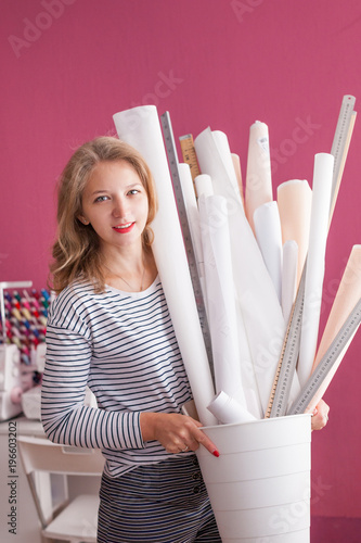 Portrait Of Smiling Woman Wearing Apron Holding Rolls Of Craft Paper