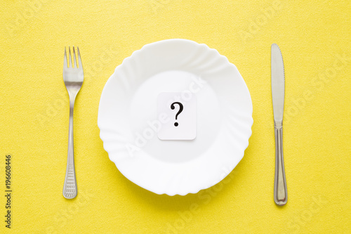 Clean, empty, white plate, fork and knife with yellow tablecloth on a table. Question mark. Starving people. Meal waiting concept. Flat lay. Top view.