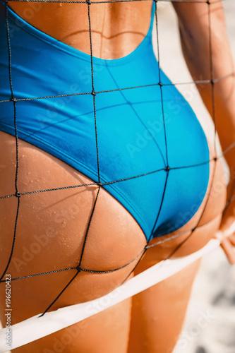 Foto  Attractive woman body in bikini with tennis net on sandy beach.