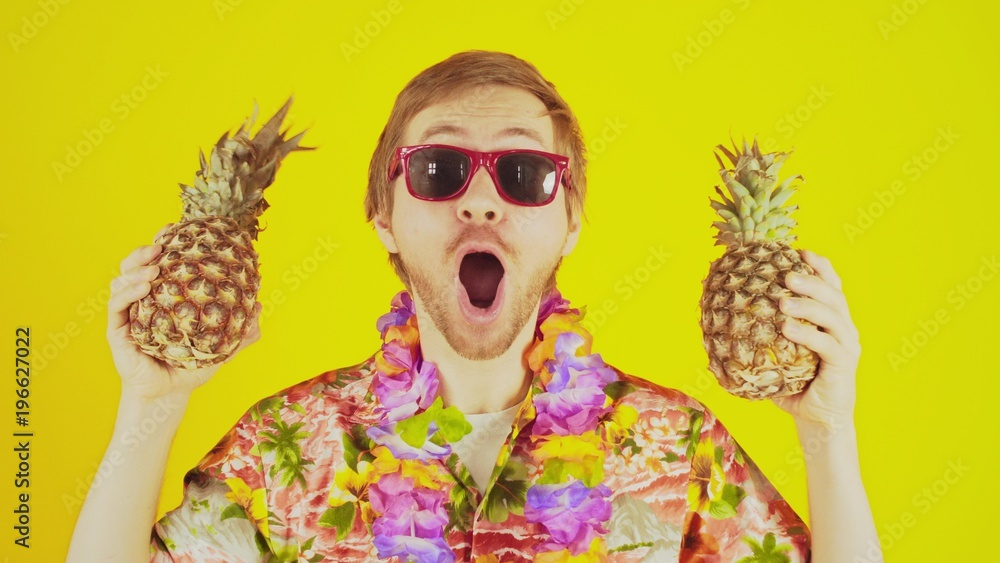 Fototapeta Happy lucky young man standing on yellow background with hawaiian shirt and two pineapples