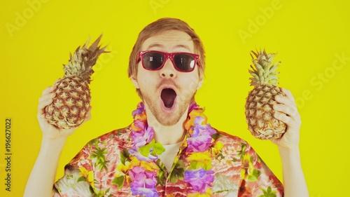 Szczęśliwy szczęście młody człowiek stojący na żółtym tle z koszula hawajska i dwa ananasy