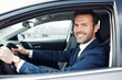 Portrait of smiling businessman driving car