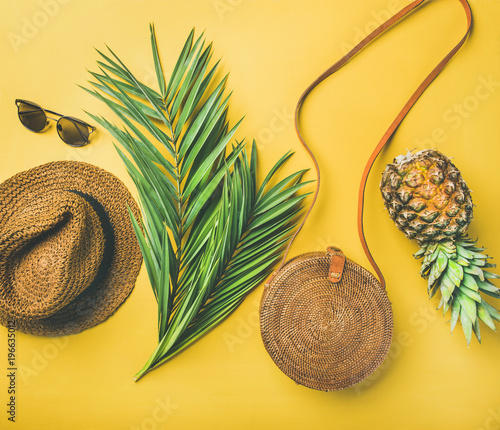 Colorful summer female fashion outfit flat-lay. Straw sunhat, bamboo bag, sunglasses, palm branches and pineapple over yellow background, top view. Summer vacation fashion or travel concept Wall mural