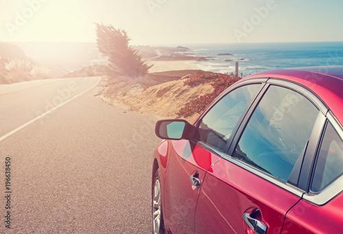 Fototapeta Red car close-up on the road near the ocean obraz