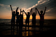 group of six children raised their hands up silhouettes at sunset beach