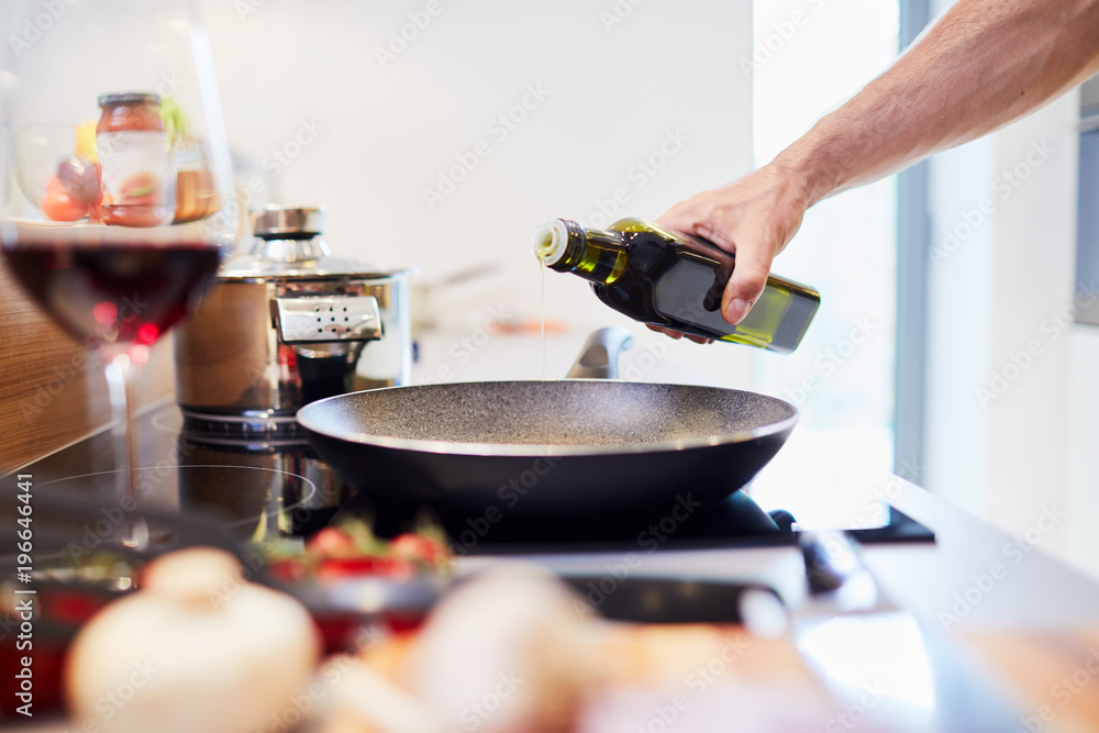 Fototapety, obrazy: Close-up of male hand pouring oil into pan in the kitchen