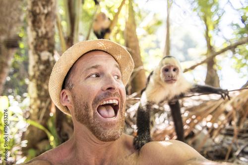 men tourist makes selfie self portrait with monkey Fototapeta