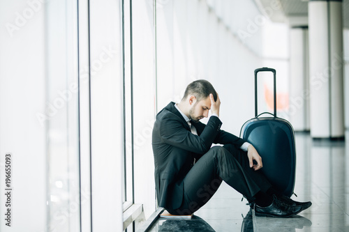 Fotografía  Business man sitting at the terminal airport on the floor with suitcase flight delay, two hands touch at head, headache, waiting traveling