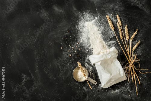 Fototapeta Flour bag, ears of wheat and measuring cup on black background obraz