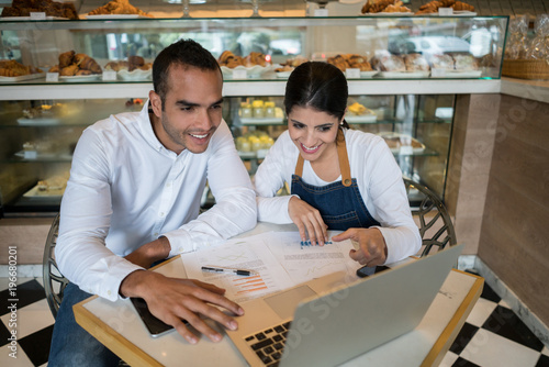 Tuinposter Bakkerij Business owner of a bakery and female administrator sitting checking the bookkeeping on the laptop both smiling