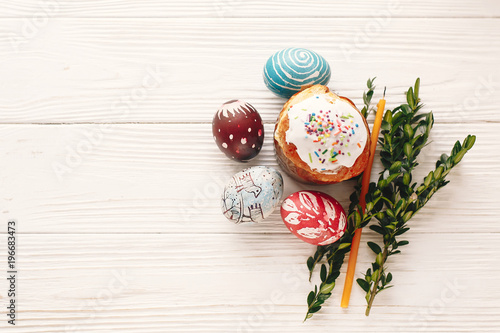 Stylish painted eggs and easter cake on rustic wooden background stylish painted eggs and easter cake on rustic wooden background with spring flowers and candle m4hsunfo