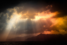 Dramatic View Of Nature. Black Stormy Sky Over Sea And Mountains With Sun Rays Through Clouds. Salerno, Italy