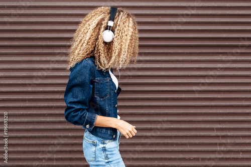 Pretty young curly hair blonde woman posing on the street happy lifestyle portrait in summertime