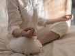 Unrecognizable woman meditating on bed