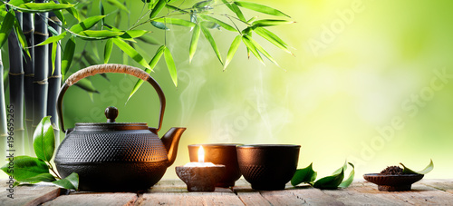 Black Iron Asian Teapot and Cups With Green Tea Leaves