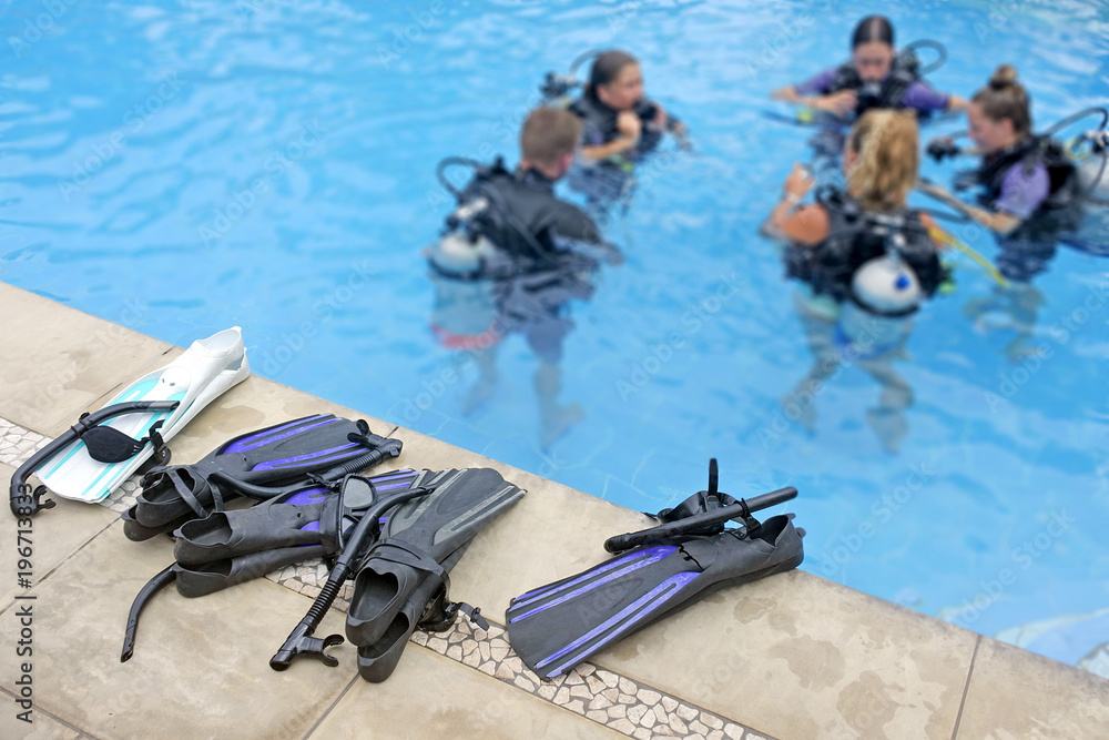 Fototapeta Unrecognizable group of people learn to scuba dive in a pool
