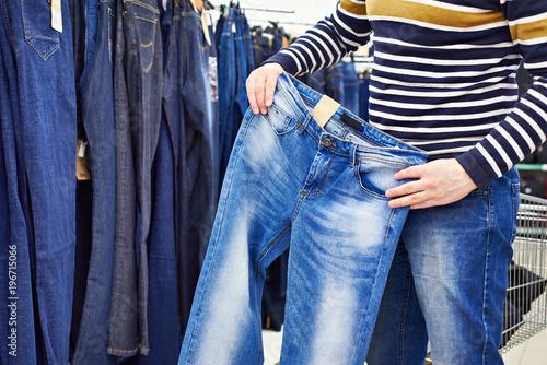 Photo sur Aluminium Aquarelle avec des feuilles tropicales Man chooses blue jeans in shop