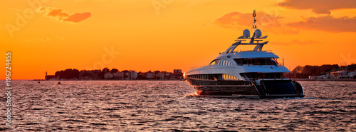 Fotografia Yachtig on open sea at golden sunset panoramic view