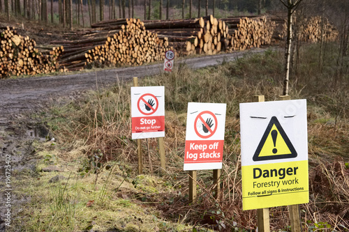 Tuinposter Oude verlaten gebouwen Forest felling safety sign keep off chopped wood stacks in woodlands wilderness