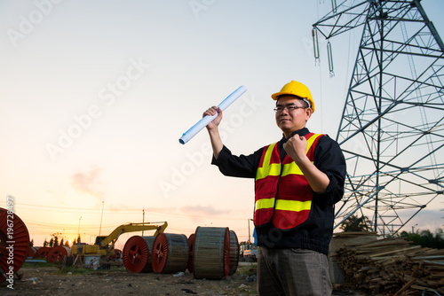 Electrical engineer working electrician holding blueprint at high electrician holding blueprint at high voltage power pylon against blue sky malvernweather Choice Image