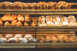 different fresh bread on the shelves in bakery
