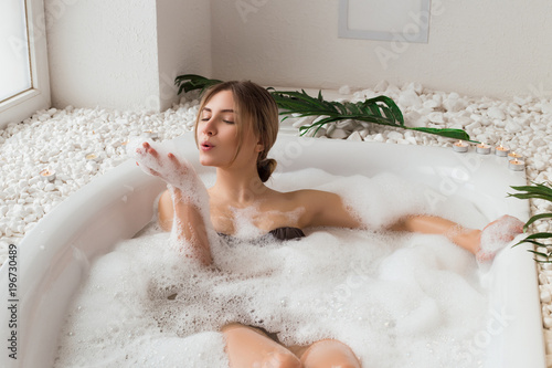 The place that leaves you feeling great! Attractive enjoying young girl blowing at the soap foam in the bath and having a great leisure time, while relaxing Fototapeta