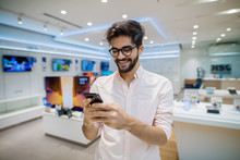 Close Up Portrait View Of Satisfied Excited Happy Smiling Young Student Bearded Man With Eyeglasses Looking At Mobile In A Tech Store.