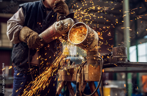 Profesional fabric worker in protective uniform cutting metal pipe on the work table with an electric grinder in the industrial workshop Wallpaper Mural