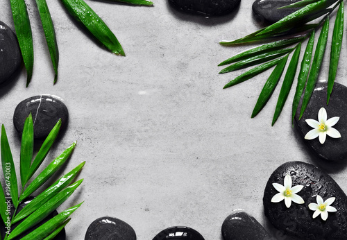 Poster de jardin Spa Grey spa background, palm leaves and black wet stones, top view