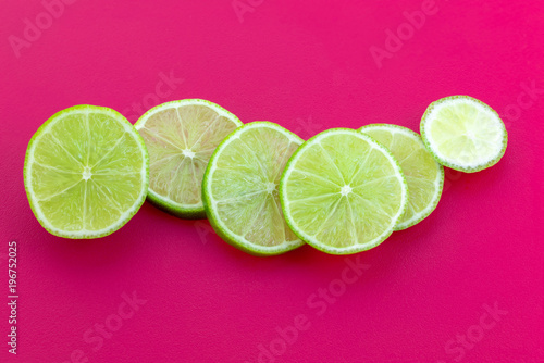 Slices Of Green Lemon Placed On Complementary Color Pink Background