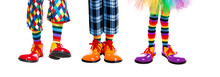 Three Clowns Legs In Clown Shoes Of Different Colors Isolated On White