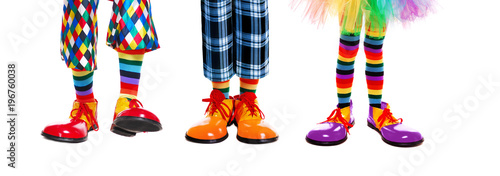 Valokuva Three clowns legs in clown shoes of different colors isolated on white