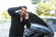 angry man calling by phone with damaged car