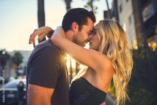 Obraz na plátně romantic couple kissing on sidewalk in los angeles