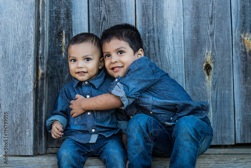 Valokuva  two latino children sitting on a stair case