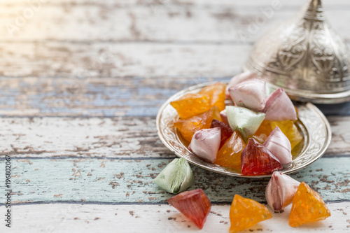 Akide (sugar) candies on old metallic plate on vintage table