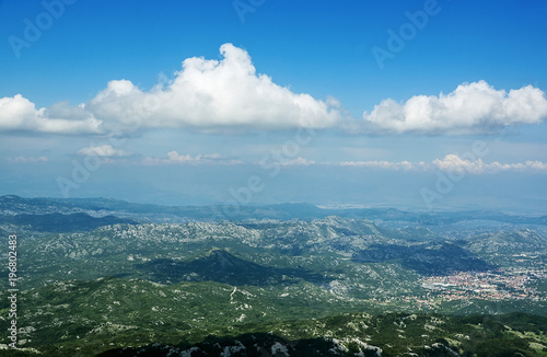 Top view in sunny day on mountains and beautiful curly-headed white clouds Fototapeta