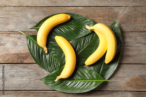 Fresh ripe bananas with leaves on wooden background