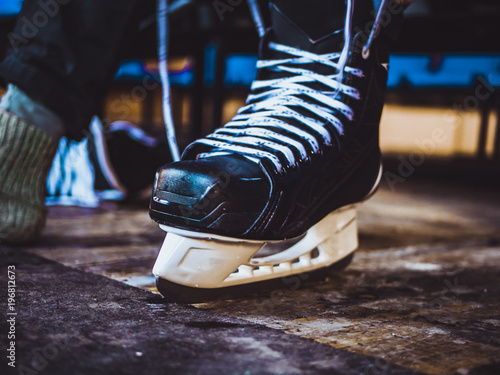 Cadres-photo bureau Jogging close up shot of hand tie shoelaces of ice hockey skates in locker room