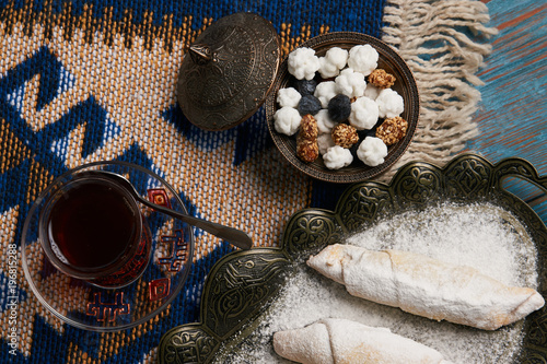 Tuinposter Boeddha Homemade Mutaki roll cake with walnuts and sugar powder, oriental sweets mutaki pastry and traditional glass of black tea on rustic wooden blue table background, close-up